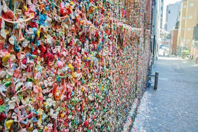 """Post Alley, Seattle, Mỹ: Bức tường kẹo cao su sặc sỡ là điểm nhấn của con phố này hình thành vào đầu những năm 1990 khi hàng dài người sốt ruột chờ đợi mua vé xem hài kịch ở nhà hát Seattle Theatresports. Lúc đầu, người ta gắn kẹo cao su cùng với đồng xu nhỏ vào tường, nhưng theo thời gian, các đồng xu bị cậy mất và chỉ còn lại bã kẹo cao su. Ngày nay, nhai kẹo cao su rồi trét bã lên tường dường như đã trở thành """"nghi thức"""" của du khách khi đến đây."""