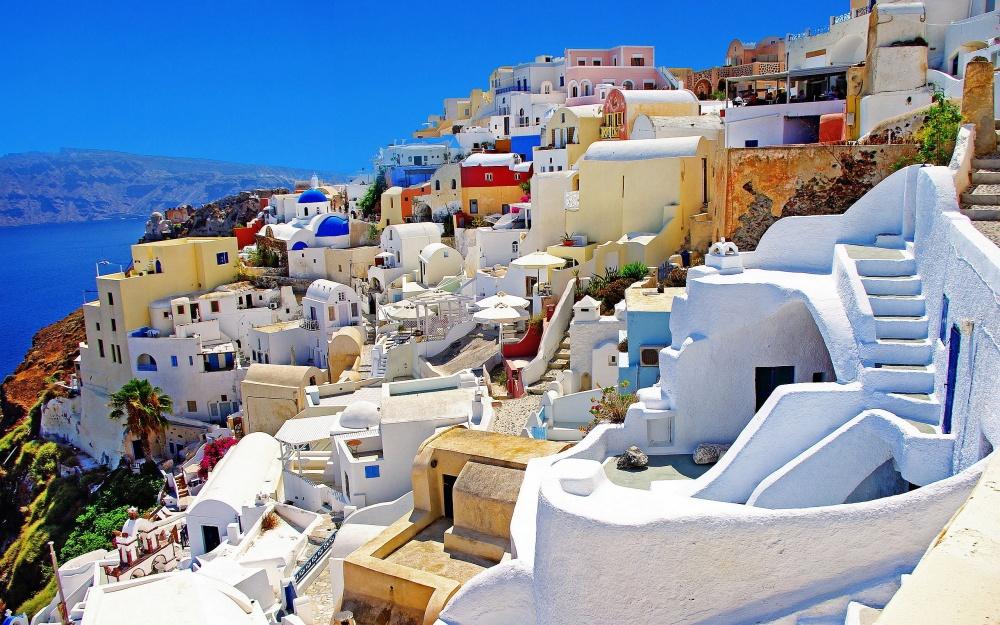 Santorini bên bờ biển Hy Lạp với tông màu chủ đạo là trắng và xanh dương, đẹp siêu thực trong ánh nắng vàng đặc trưng xứ biển