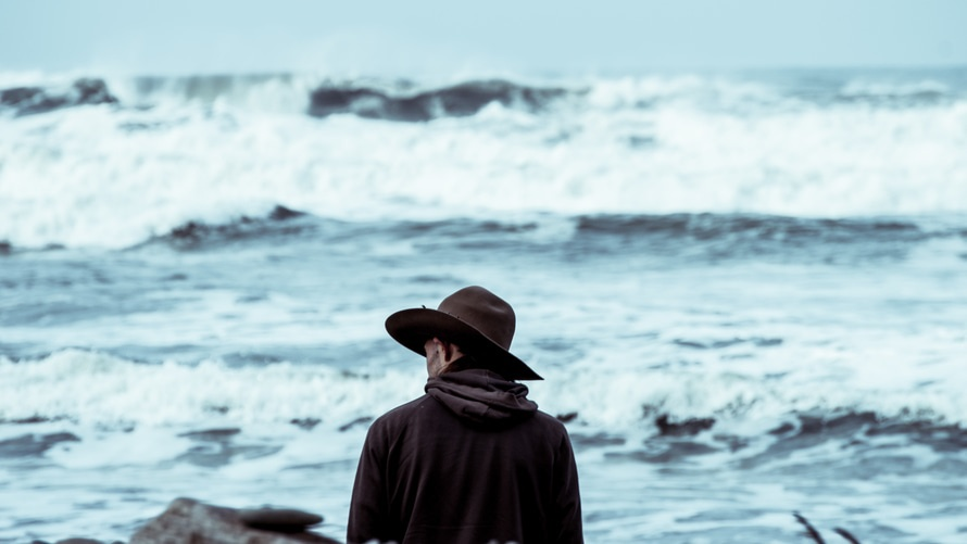 Man Wearing Black Cowboy Hat Standing in Front of Sea