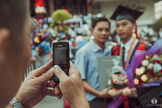 Bức ảnh cảm động: Cái ôm đầy tình cảm trong lễ tốt nghiệp và chiếc điện thoại của cha - Ảnh 2.