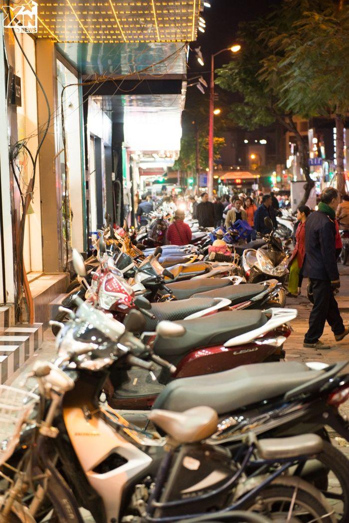 Xe cộ được xếp dài trước các cửa tiệm lớn.