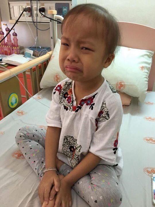 Quỳnh Chi khóc òavì sợ bị tiêm, đôitay bé nhỏ vội che lòng bàn chân trắng bệchthiếu máu.