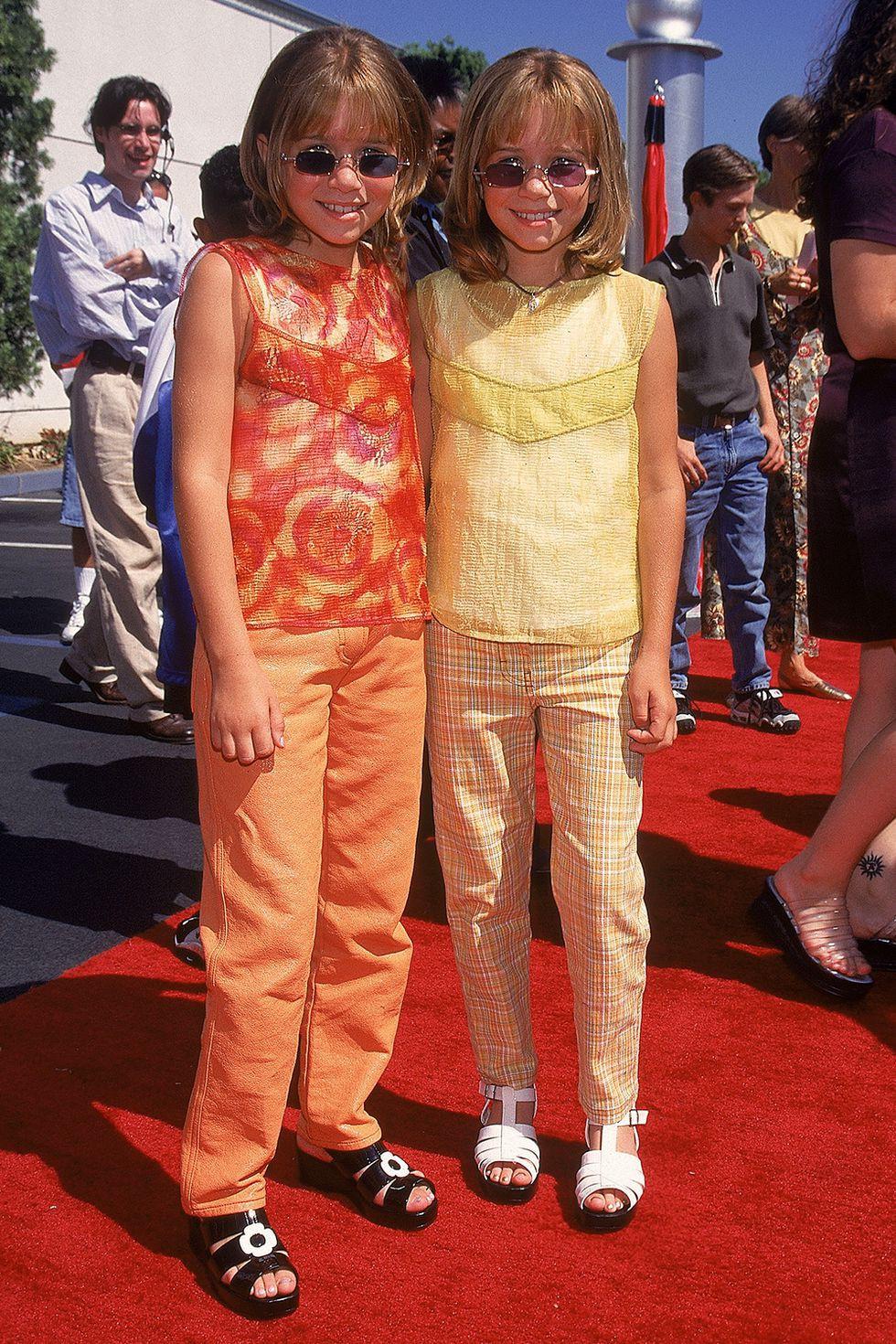 Cặp chị em sinh đôi Mary-Kate và Ashley Olsen luôn là biểu tượng thời trang đáng ngưỡng mộ của Hollywood. Và khoảnh khắc được chụp vào năm 1997 cho thấy từ nhỏ, hai chị em đã sở hữu gu thời trang và thần thái hơn người trong bộ đồ lấp lánh, nổi bật với cặp kính mắt sành điệu.