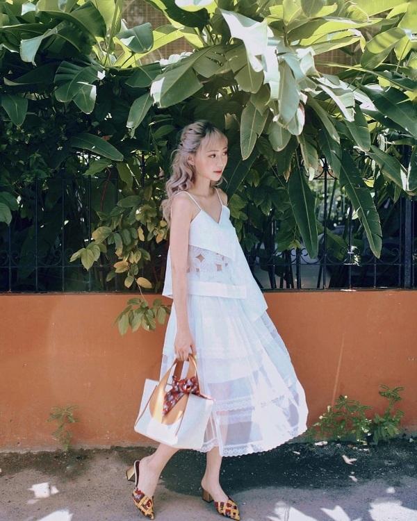 Trong những ngày hè oi ả, trang phục mang sắc trắng tinh khôi luôn là lựa chọn hàng đầu của nhiều tín đồ. Với Sun HT, cô nàng ưu ái mẫu đầm hai dây dáng suông bay bổng vô cùng mát mẻ, thoải mái. Để tăng thêm nét nổi bật cho phong cách, cô phối cùngphụ kiện túi xách và giày hở gót đồng điệu.