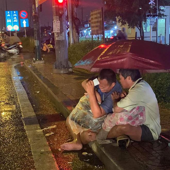 Xót xa hình ảnh 2 người đàn ông khiếm thị che chung chiếc ô dưới cơn mưa Sài Gòn để bán từng chiếc vé số - Ảnh 1.