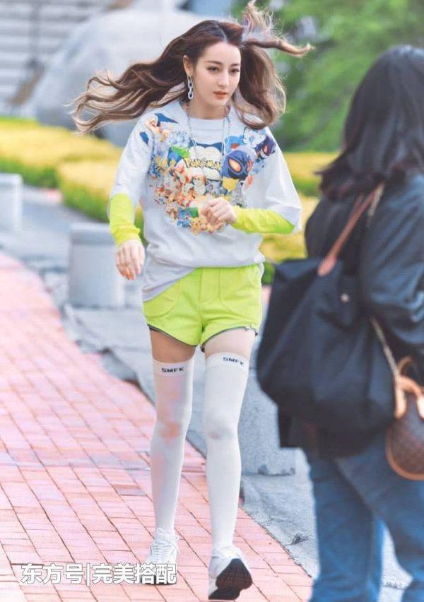 Chói lóa trong set áo đồ bộ màu xanh chuối mix với áo thun pokemon ở ngoài cùng kiểu vớ cao qua đầu gối trong một chương trình truyền hình thực tế