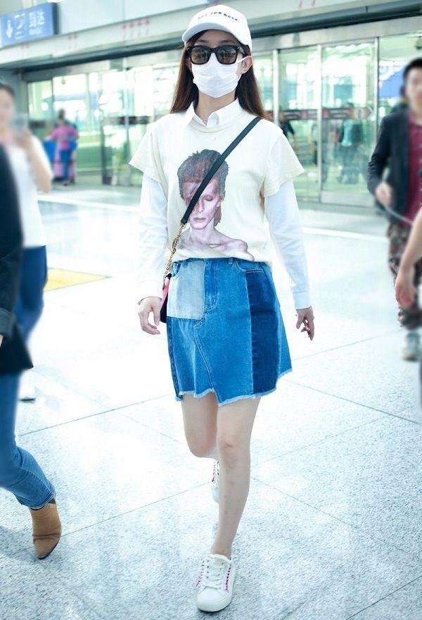 Nàng bánh bèo yểu điệu Triệu Lệ Dĩnh chọn áo sơ mi trắng mặc bên trong mix cùng áo thun bên ngoài mix phối cùng váy jeans và giày thể thao khi ở sân bay