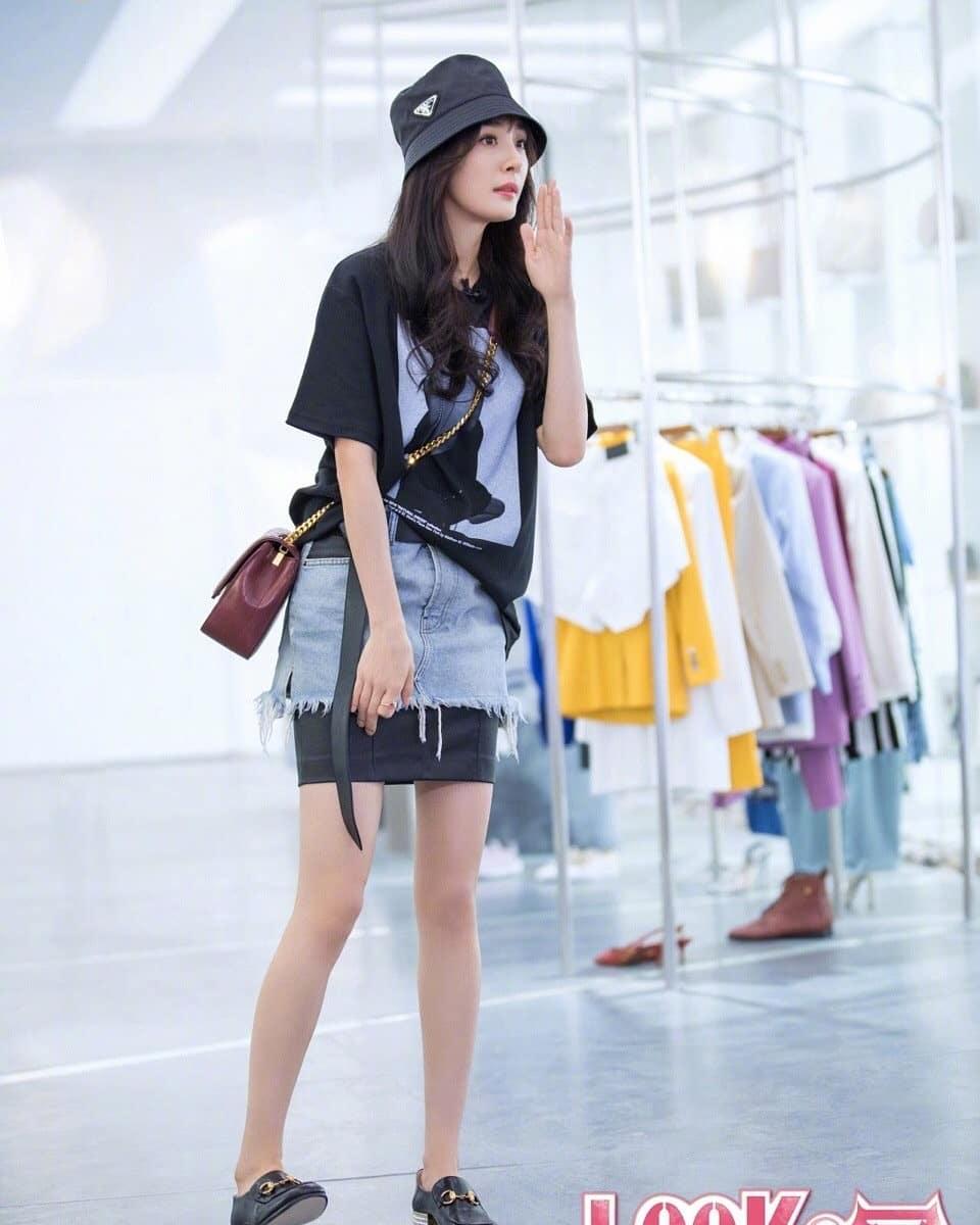 Dương Mịch mặc áo đen cùng chân váy denim và đội nón đen