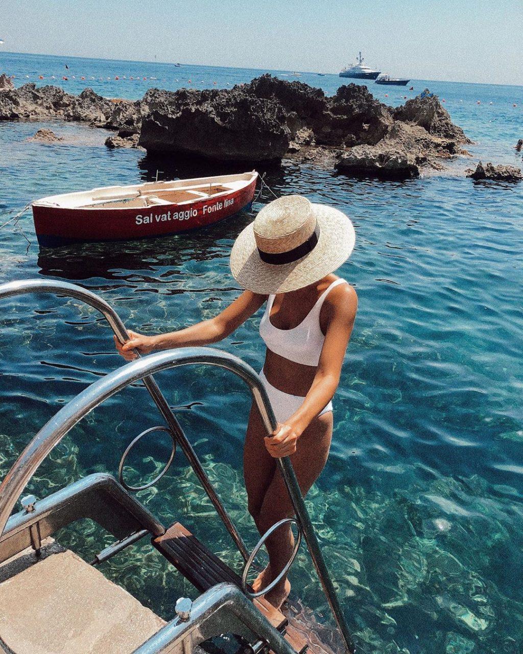 Fashionista mặc bikini cạp cao màu trắng đội mũ trắng