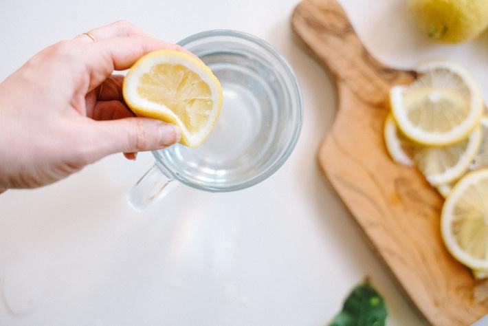 hand-squeezing-lemon-water