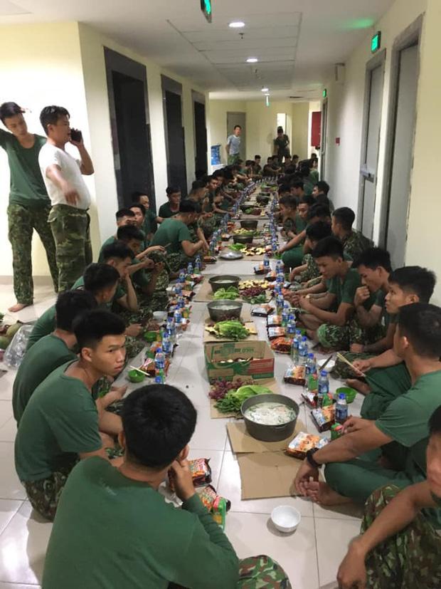 Bữa ăn khuya đạm bạc của các chiến sĩ bộ đội bên trong khu cách ly sau 1 ngày căng mình chống dịch Covid-19: Nổi cháo trắng, gói bim bim cùng chai nước lọc lót dạ - Ảnh 3.