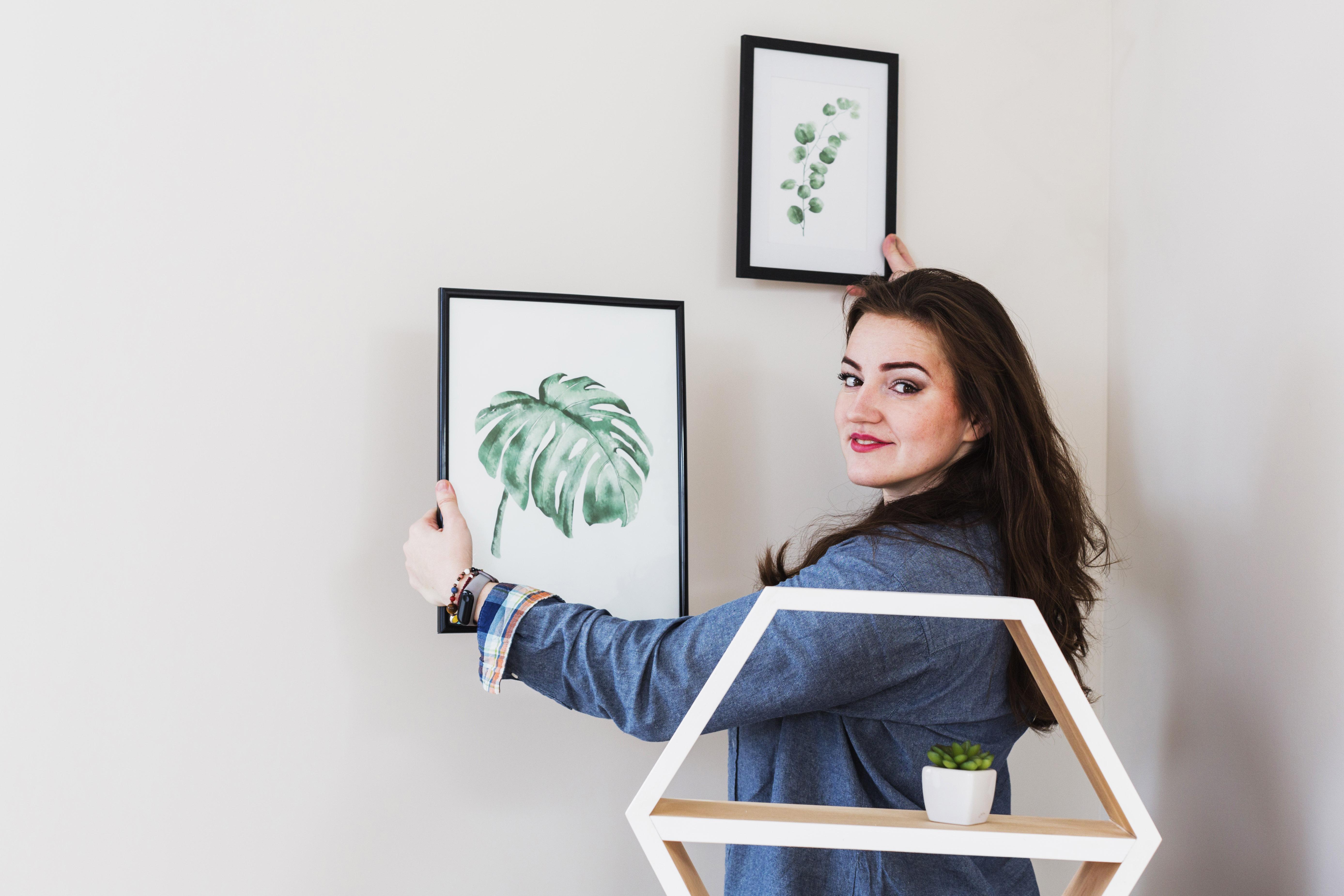 cô gái treo tranh trên tường