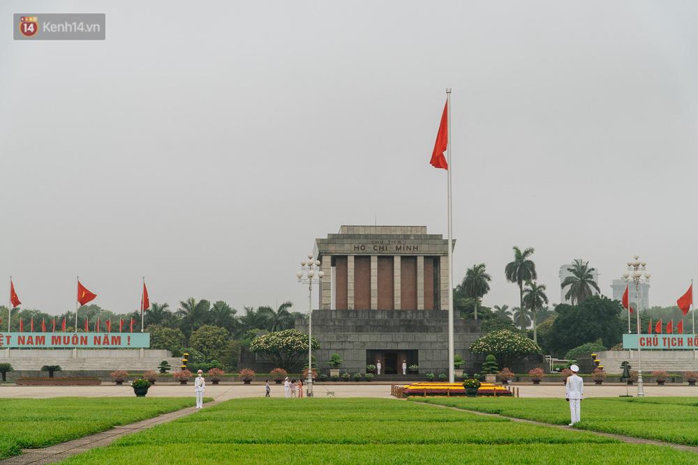 130 năm sinh nhật Bác Hồ: Người Hà Nội đến dự lễ chào cờ ở Quảng trường Ba Đình lịch sử, phố phường rực rỡ cờ hoa - Ảnh 1.