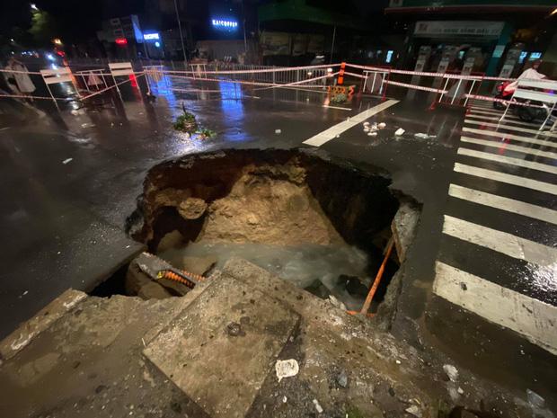 Sau cơn mưa lớn, xuất hiện hố tử thần khổng lồ ngay ngã tư ở Sài Gòn - Ảnh 1.