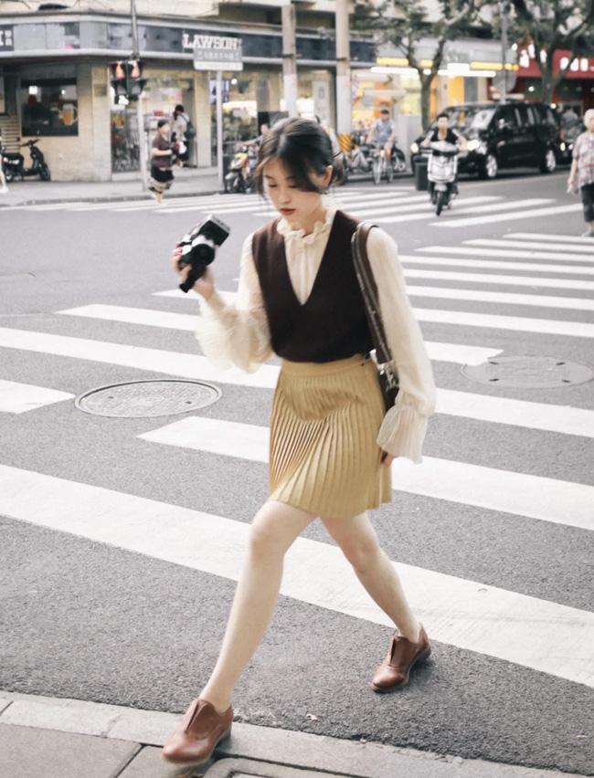 Cô nàng này có cách layer áo len ba lỗ cùng áo blouse và chân váy xếp ly rất đáng để học theo. Nếu không có loafer, bạn có thể thay bằng một đôi cao gót cơ bản màu đen.